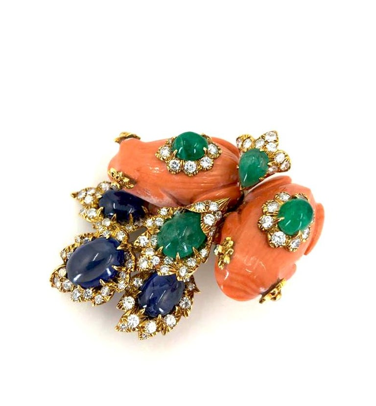 A fantastic vintage David Webb gem-set brooch in 18k gold; designed as two carved coral frogs set with diamonds and cabochon emeralds, within a spray of four diamond encrusted leaves, set with large cabochon sapphires and emeralds.  Accompanied by a
