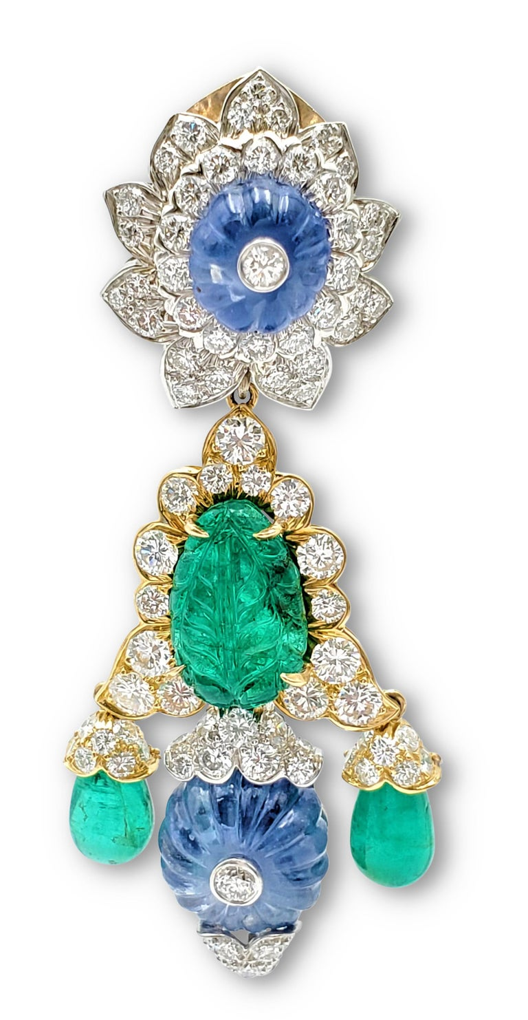 An impressive pair of earrings designed by David Webb. Easily converted from day-to-night, the earrings feature two detachable drops. Crafted in 18 karat yellow gold and platinum, the earrings center on carved emeralds, carved sapphire fluted beads,
