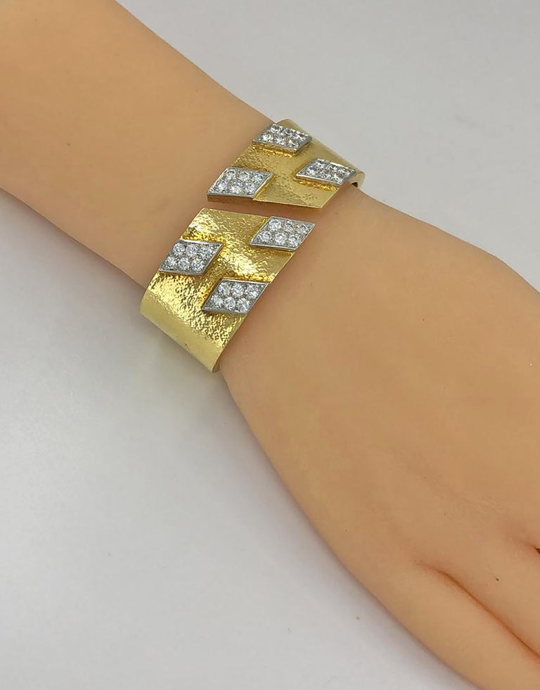 DAVID WEBB Diamond Spring Cuff Bracelet in 18k Yellow Gold and Platinum.  A David Webb wide spring bracelet textured with emblematic tactile gold, adorned with six slanted geometric panels of platinum set with diamonds. The bracelet appears heavy