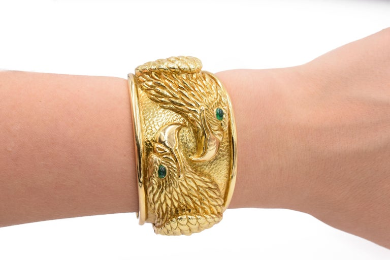David Webb Gold and Emerald Eagle Cuff Bracelet This bracelet has oval cabochon emeralds, in the eyes of two eagles designed in hammered and sculpted 18k gold.  Diameter: 2 1⁄4 inches. Wrist size: 7 inches