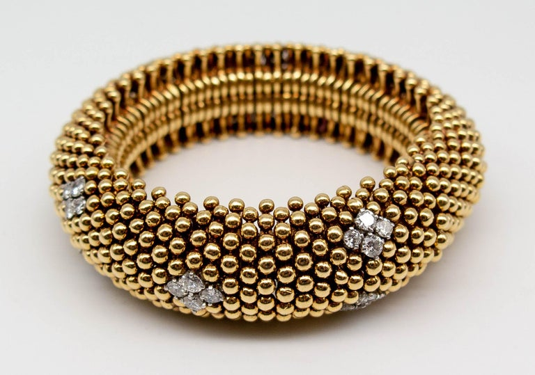An exceptionally well constructed and wearable bracelet signed David Webb, probably dating from the 50's or 60's.  Minute balls of 18 karat gold are aligned in rows around the wrist, interspersed with diamond quadrants evenly positioned around the