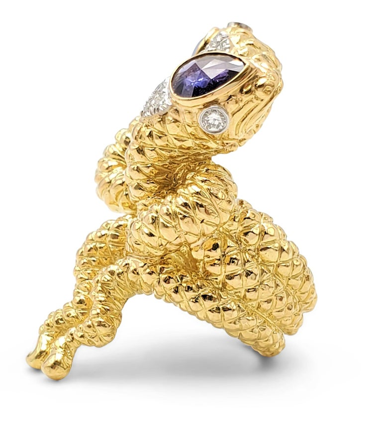 A striking ring designed by David Webb centering on two intertwined serpents crafted in textured 18 karat yellow gold. Each serpent head is set with a sapphire weighing an estimated 0.80 and 0.95 carats each, one blue and the other purple in hue.