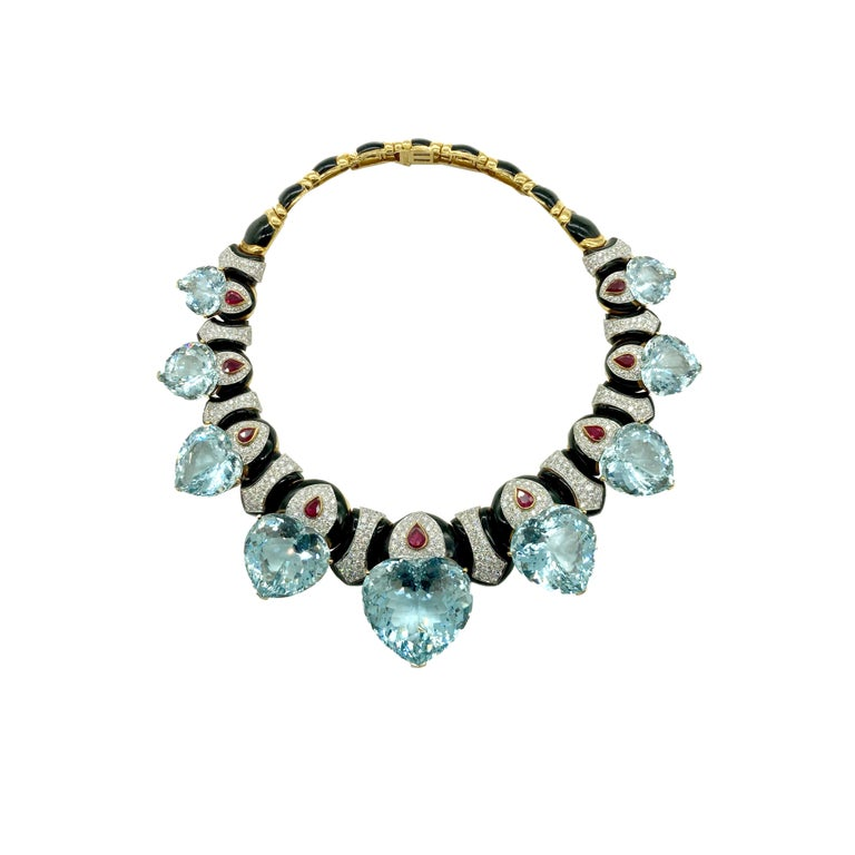 An exquisite David Webb demi-parure comprised of a necklace and earclips in 18 karat yellow gold, featuring chunky heart-shaped aquamarines, pear-shaped rubies, black onyx, and diamonds. Circa 1970.