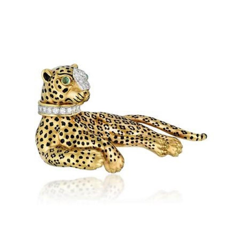A beautiful and classic David Webb animal brooch of a lounging leopard, crafted in 18k yellow gold with black enamel spots, a diamond collar and snout, with emerald eyes.   The leopard lounges languidly, the diamond studded collar and snout dazzling