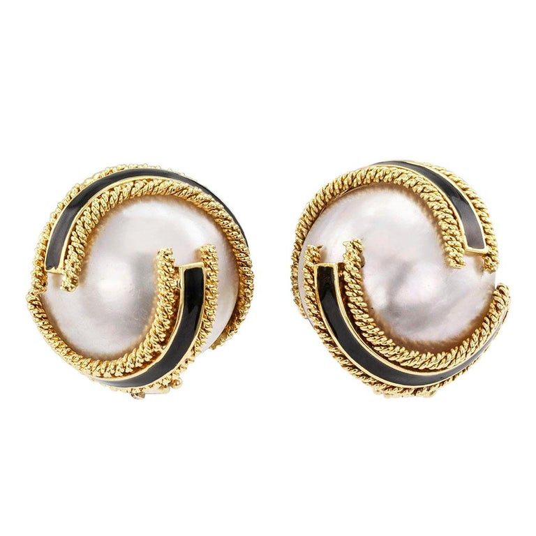 David Webb mabé pearl and black enamel ear clips circa 1960. The matching designs feature a pair of mabé pearls, each measuring approximately 19 mm, enveloped in crisscrossing ribbon motifs of black enamel with corded gold borders, mounted in