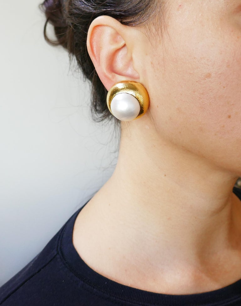 Bold yet elegant earrings created by David Webb in the 1980s. Classy and wearable, the earrings are a great addition to your jewelry collection. The earrings are made of 18 karat (stamped) yellow gold and feature a mobe pearl.  The earrings measure