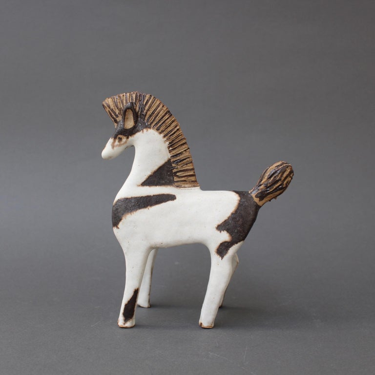 Set of two ceramic horses by Bruno Gambone, circa 1970s. Untamed, free and strapping, these two ceramic horses were created in Gambone's signature chalk-white glaze - one with the addition of dark brown markings on the mane, tail and body. They are