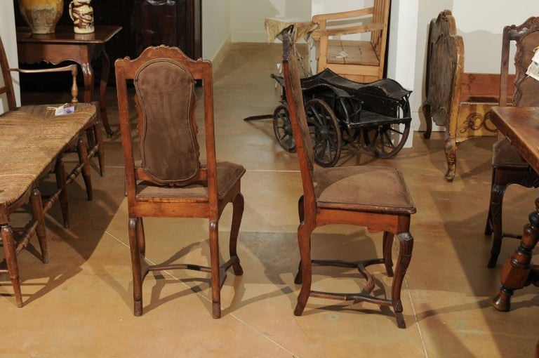 Eight Italian Roman Rococo period hand carved walnut dining room side chairs from the 18th century priced and sold in pairs, with cabriole legs, cross stretcher and brown suede upholstery. Born in the Eternal City, this collection of 18th century