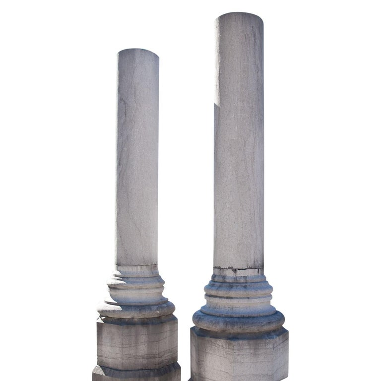 Monumental Pair of Columns on polygonal pedestals with round bases and smooth shafts.