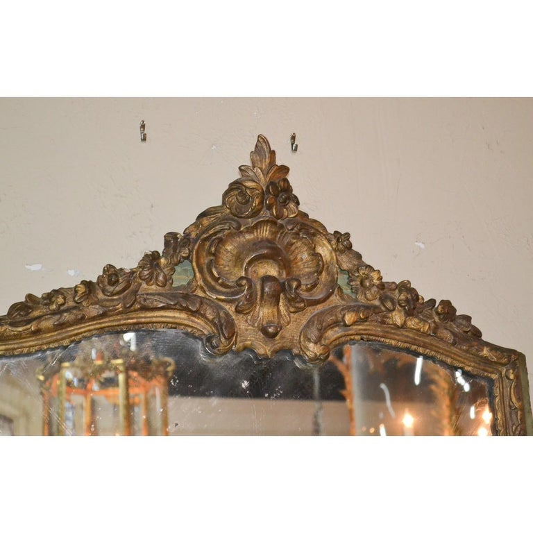 Splendid 18th century French Regence style parcel gilt wall or console mirror. The crest with finely carved leaf-sprays, shells, blossoms, and trailing flower vines. The inner border carved in relief and trimmed with a painted green-tint outer