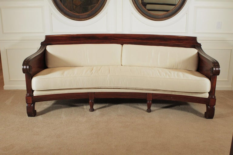 Mahogany Regency style sofa. The gorgeous hand carved frame with pillow back and seat. The fabric is somewhat worn and will need recovering. A very rare and long 97' inches long and gently curved. Dimensions: 97 W x 40 D x 39 H.