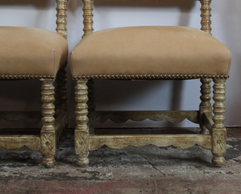 Pair of low Spanish style chairs. Carved wood frame. Upholstered in suede.
