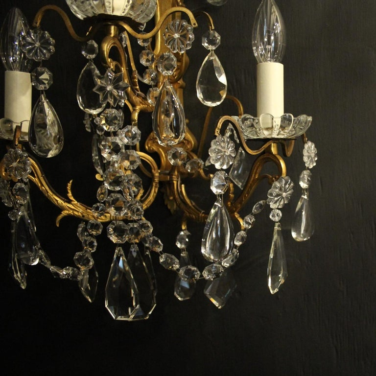 A French pair of gilded bronze and crystal triple arm antique wall lights, the detailed tiered scrolling arms with glass bobeche drip pans, issuing from a folited elongated backplate with wirework canopy and decorated overall with crystal faceted
