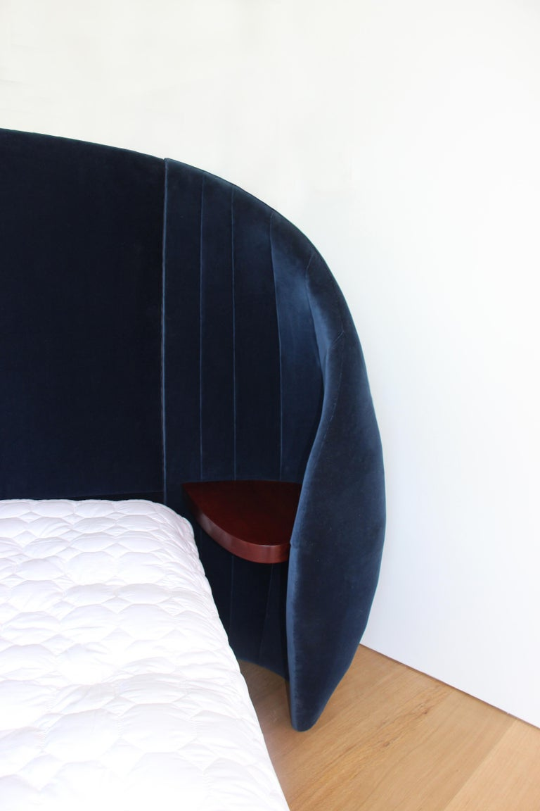 The Shell Bed is fabricated from wood, horse hair and organic latex.  The Shell form envelopes the walnut side tables while creating a sense of shelter.  Materials: organic latex foam/ wood/ upholstery and horse hair  King size headboard  NOTE: The