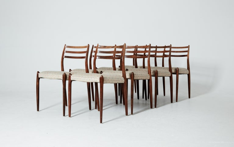 A set of eight rosewood N.O. Møller 78 side chairs. 1962 for J.L. Møllers Møbelfabrik, Denmark. Rosewood frames and fabric seat covers. We can change the seat covers to leather, vinyl or cord if you wish.