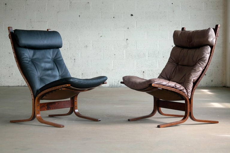 Fantastic set of easy/lounge chairs designed by Ingmar Relling for Westnofa in 1965. One chair is in black leather and the other in grayish brown and while not matching in color they compliment each other perfectly. Both chairs have matching frames