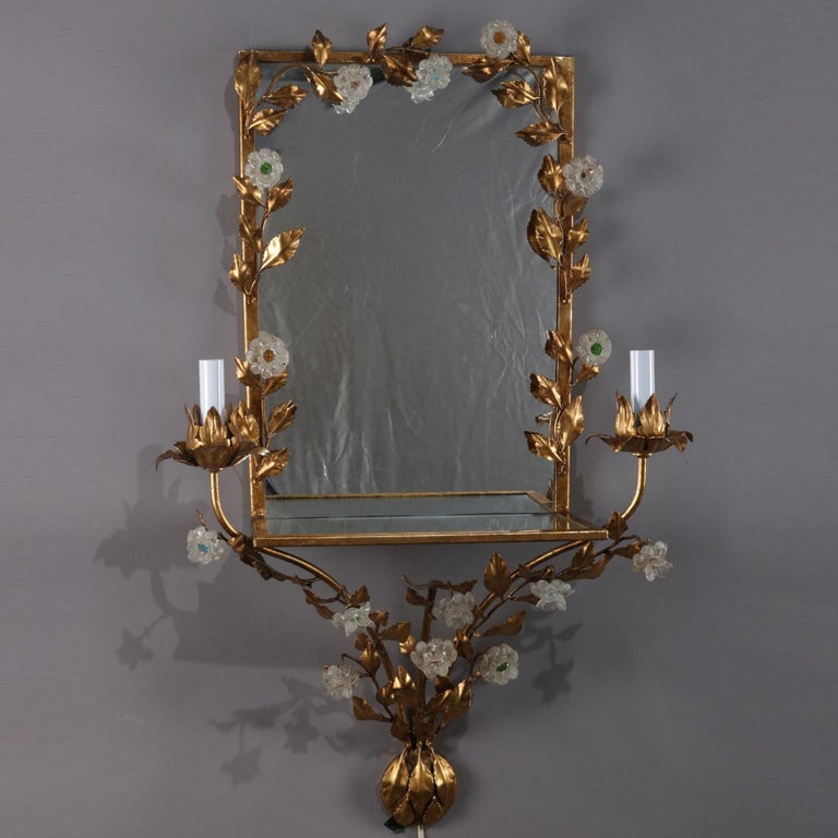 Vintage Italian candle light sconce features mirror with gilt metal frame decorated in foliate leaf and vine having attached crystal flowers and terminating at base with gathered bouquet, mirrored display shelf is flanked by electric candle lights