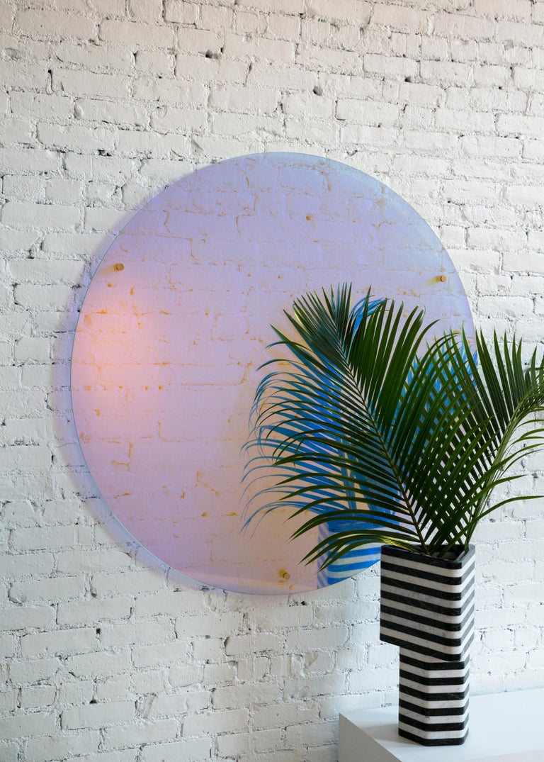 This unique wall mounted piece is as much a statement art piece as it is a mirror. Made of the highest quality dichroic glass the color shifts when viewing from different angles and throughout the day as changes in natural light intensity and color