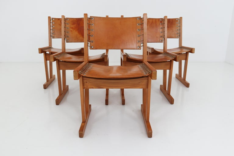 Set of five safari chairs in absolutely gorgeous thick cognac saddle leather and solid pinewood, circa 1970s. Chairs are in very good condition with incredible patina and natural wear to the leather adds tons of character.