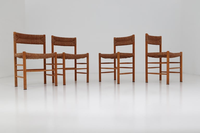 A pair of four dining chairs of wood and straw in one of the quintessential midcentury designs of their creator, the famous French furniture maker Charlotte Perriand. The four chairs are identical in the patina as in their very uniform state. These