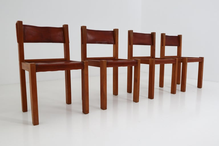 Set of four leather and elmwood dining chairs. Made in France, 1960s.