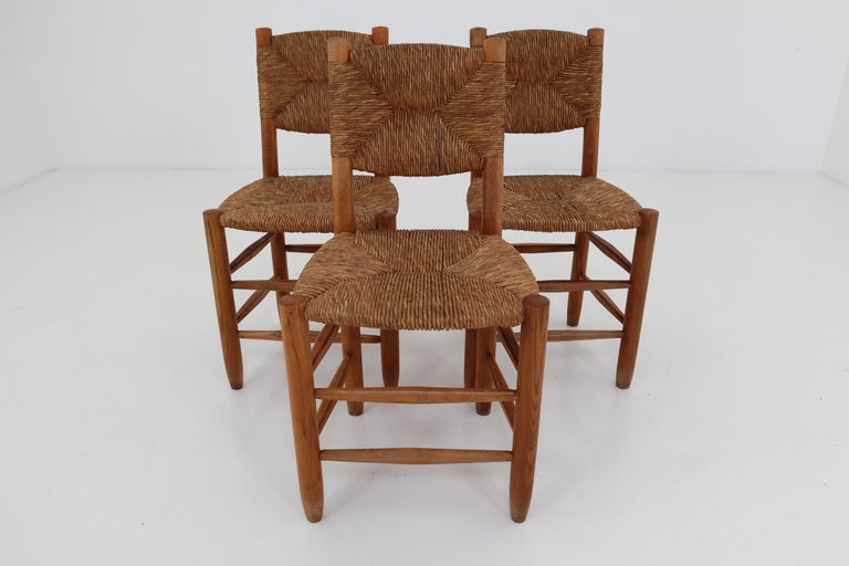 A pair of three dining chairs of wood and straw in one of the quintessential midcentury designs of their creator, the famous French furniture maker Charlotte Perriand. The three chairs are identical in the patina as in their very uniform state.