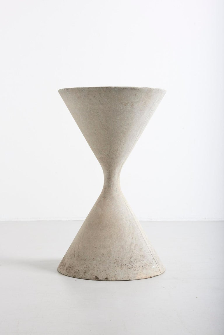 This hourglass shaped planter was created in the 1950s by Swiss Industrial designer, Willy Guhl. It is called the 'Spindle Planter'. Willy Guhl created the planter together with his students for a project assignment by the Swiss company Eternit in
