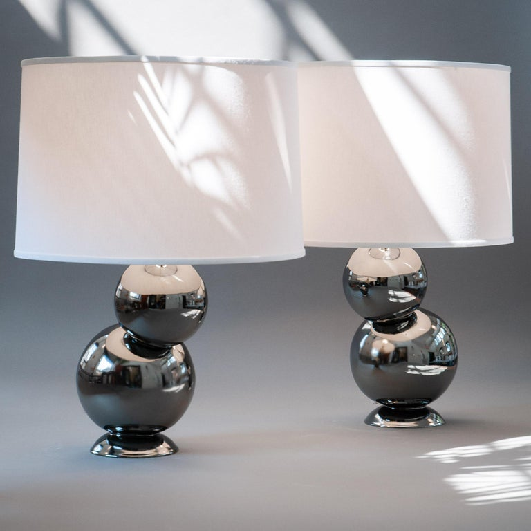 Our homage to Space Age design, the platinum bubble table lamp pair in stoneware is divine whether bookending a credenza or topping off nightstands. Assembled by hand from stoneware orbs that are placed offset from their base, and finished with a