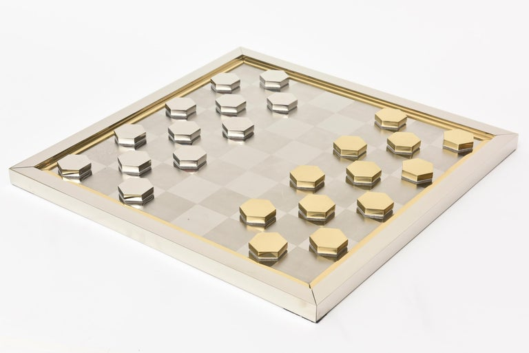 This ultra chic and modern signed Italian Romeo Rega checkers game has sculptural components. It is great just even as a decorative object or for real playing checkers. It is from the 1970s. The board is square with a brass inner lip. It is signed