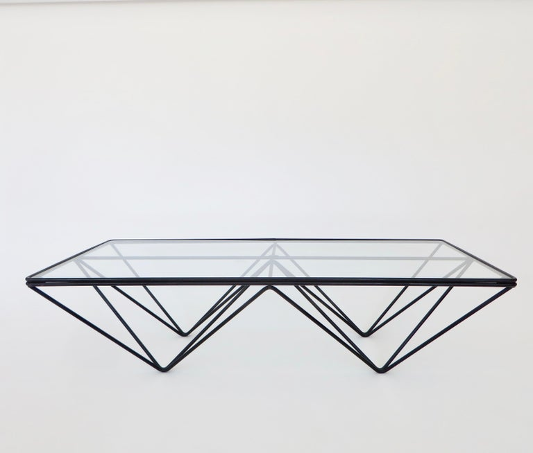 A coffee table in the style of the Alanda low coffee table by Paolo Piva of welded black enamel steel rods with a new glass top.  Welded enameled steel rods with a glass top. This could be used as a small coffee table or a side table. New glass.