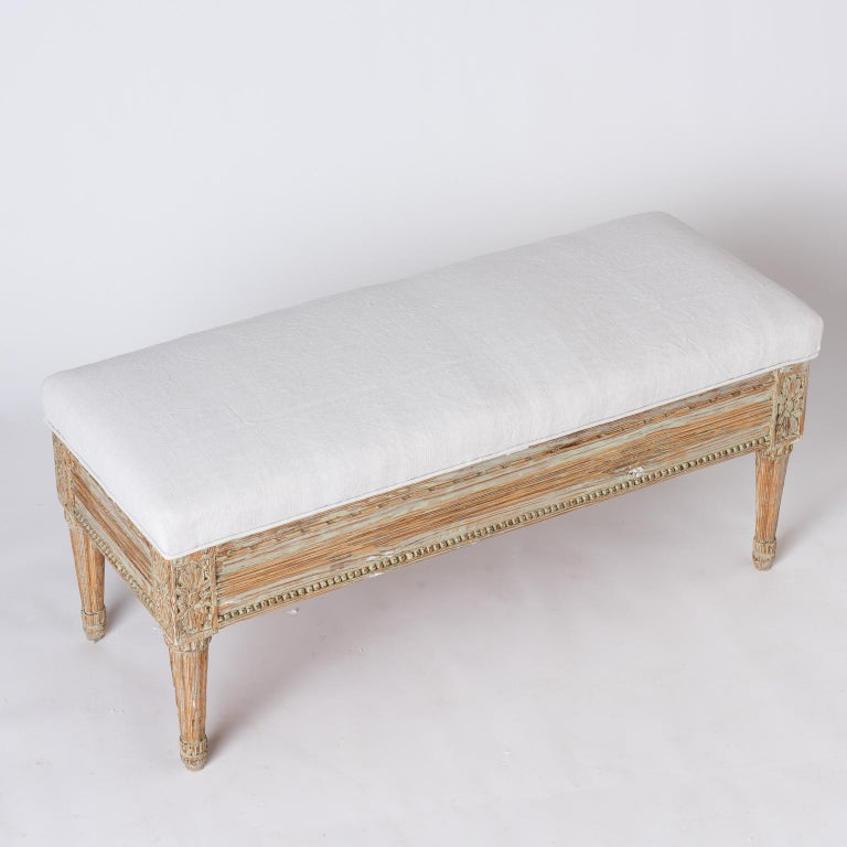 This useful and charming bench has detailed carvings with flowers on the front sides, and nicely tapered legs. The top opens to reveal plenty of storage, and beautiful old iron hinges. The paint surface is original. This piece could also be used as