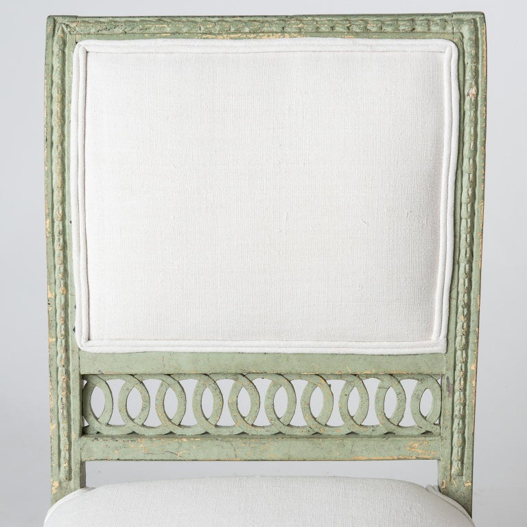 Although not marked, these chairs are likely from Stockholm due to the openwork at the back. They have detailed carving framing an upholstered back, and elegant front legs with acanthus leaf carvings which are typical of the Gustavian period. The