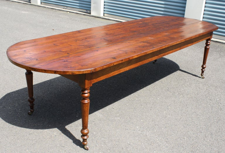 A rare and highly unusual demilune-ended farmhouse or refectory table, on four Sheraton-esque turned and castered legs. Accommodating 12 for dining with minimal interference of table legs and 24 inch frieze height, it appears to be of Middle