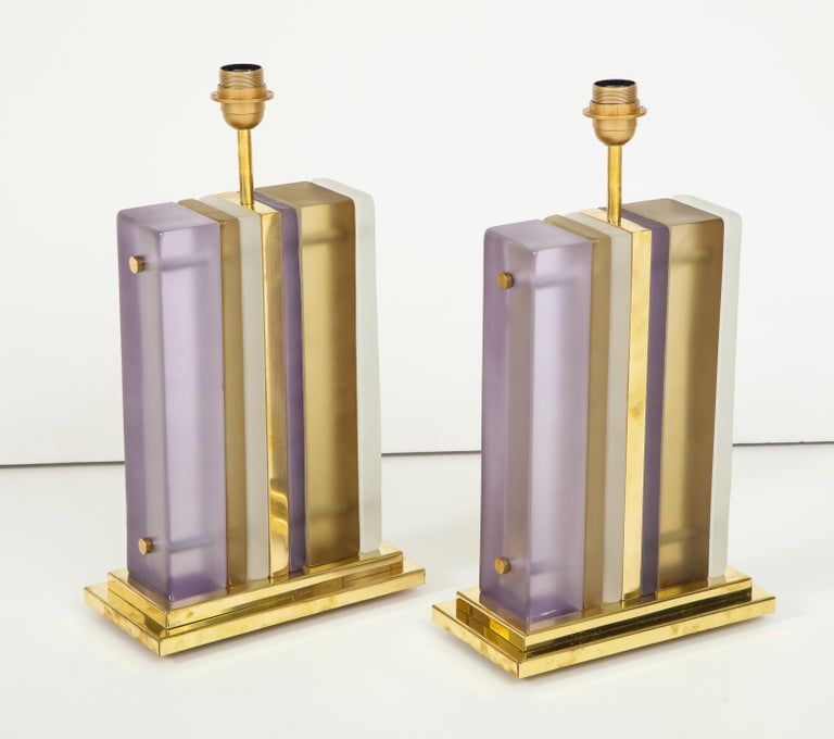 An important pair of solid Murano glass block lamps, each featuring six individually hand casted blocks of glass, varying in color from opaque white, to smoke taupe to lavender. The glass blocks flank a brass plate which extends into the central