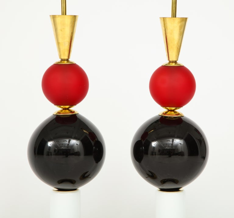 This bold pair of handblown Murano glass lamps features glass components in red, black and white. The glass alternates finishes, including a beautiful frosted finish against a glossy one. Brass cone and base add the finishing touches. These