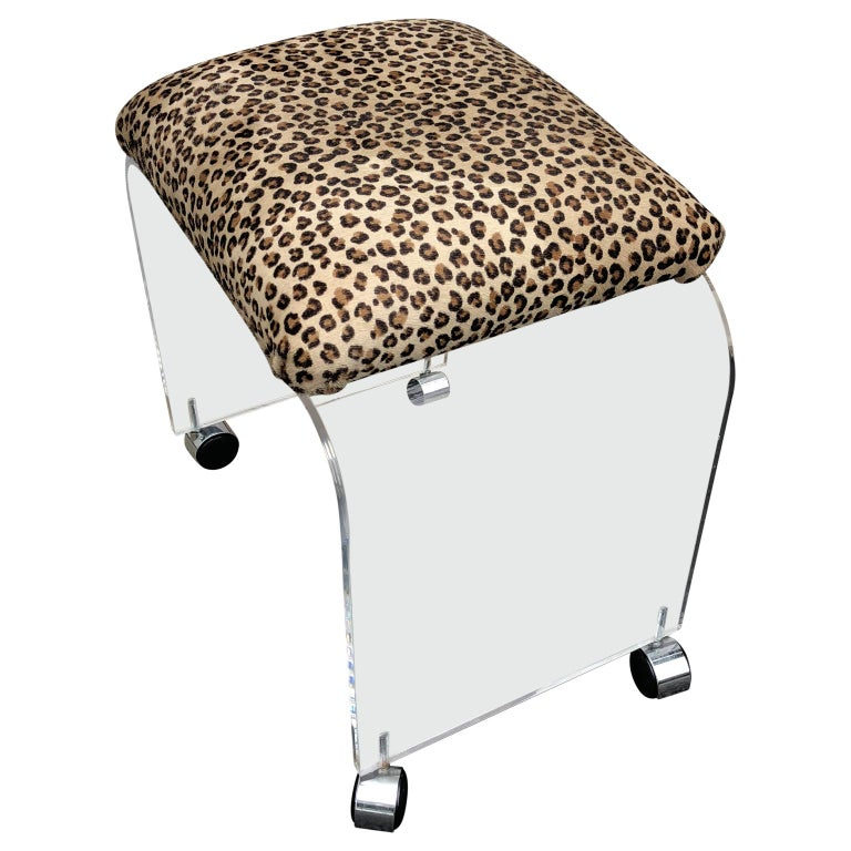 This bench or stool features a thick Lucite design with a waterfall design newly upholstered in faux cheetah fabric. It rests on castors which would make it well suited as a vanity stool. This stool is newly upholstered and on wheels.