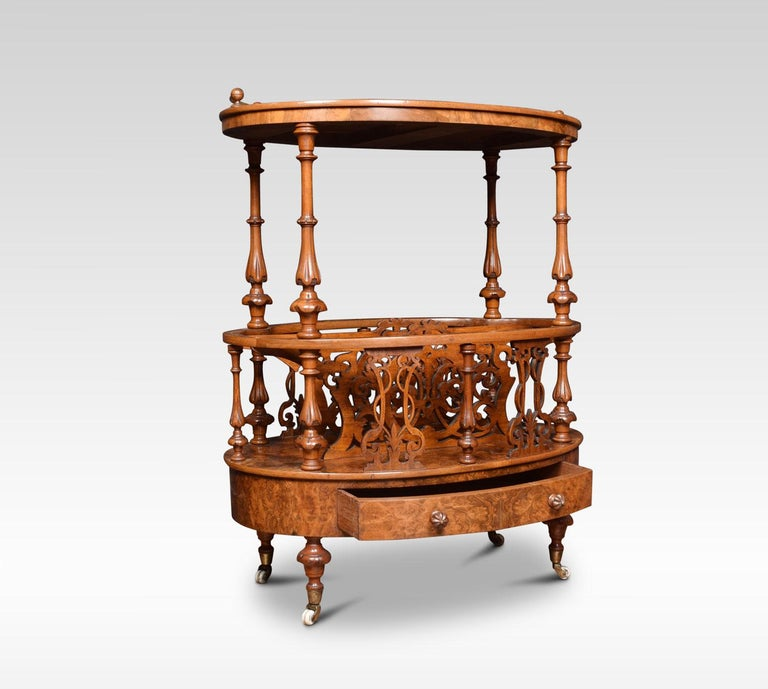 Victorian walnut and inlaid oval Canterbury, the oval top inlaid with boxwood lines and foliate arabesques with low curving brass gallery. Raised on four baluster and lappet-carved supports. The base section wit shaped and scroll fret-pierced