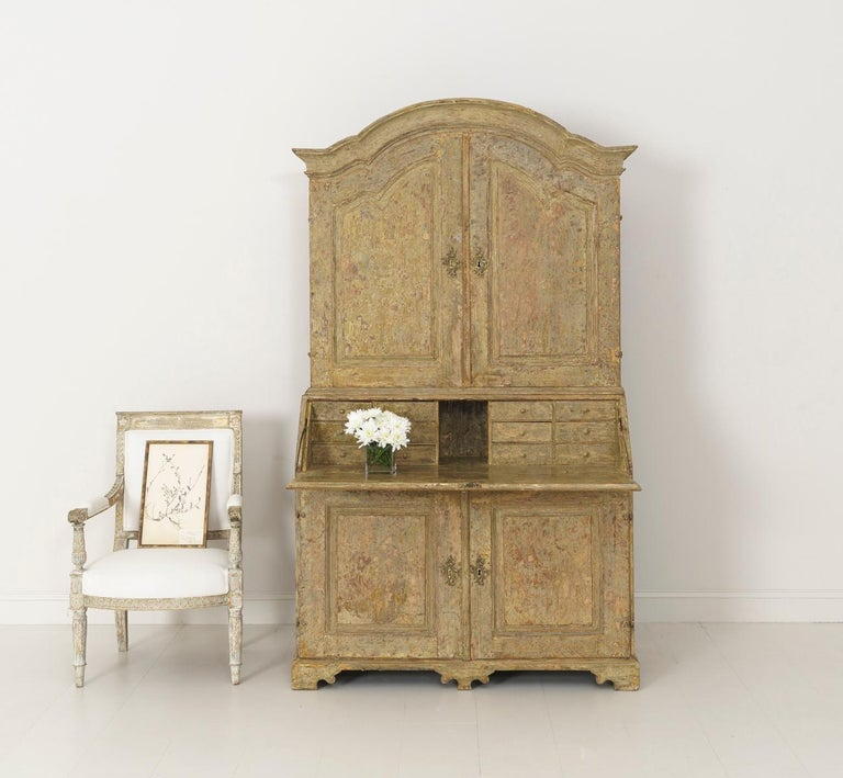 A Swedish Baroque period slant-front secretary from the 18th century in two parts with arched cornice and shaped apron. Brass hardware and original locks, circa 1770. The paint has been hand-scraped down to the original paint surface. The