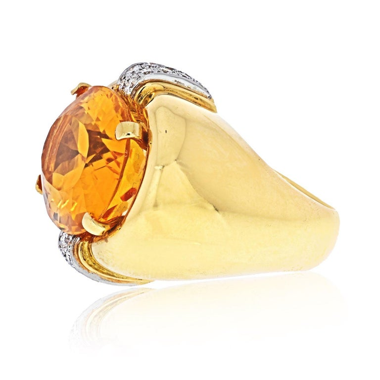 David Webb Platinum & 18K Yellow Gold Oval Orange Citrine And Diamond Ring. Set with an oval-shaped citrine weighing approximately 17.95cts and accented by round diamonds weighing approximately 0.15ct, mounted in 18k gold and platinum, size 5 1/2,
