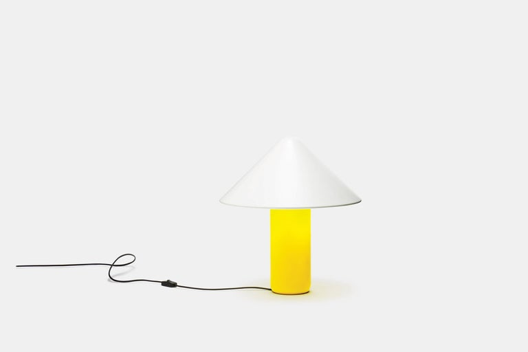 The Topp lamp draws its inspiration from two distinctive silhouettes: the classic 'Atollo' lamp by Viso Magistretti and a graphic arrow. The foot is of strong resin whose yellow colour contrasts strikingly with the white aluminium shade.   Measure: