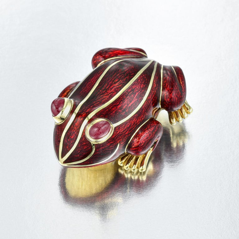 Fantastic brooch artfully sculptured in 18K yellow gold with applied with deep dark red enamel and highlighted with 18K inlaid gold accents Oval Ruby cabochon eyes set in bezels slightly above the surface Underside completed with double pin clip