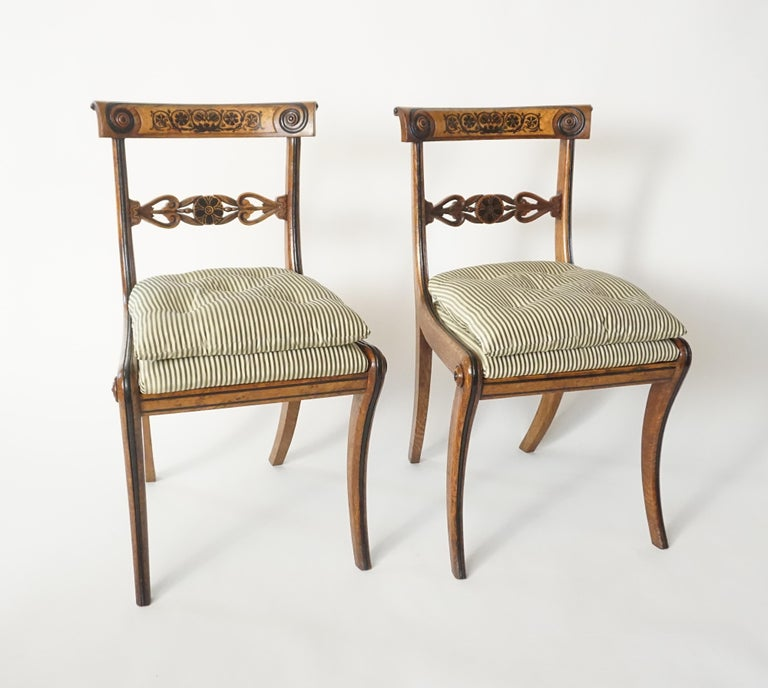 A rare and important set of four side or dining chairs by famed and short-lived English Regency-period cabinet-maker and sculptor George Bullock (c. 1782 - 1818) of klismos form; the pollard oak frames having foliate inlays of ebony with burled