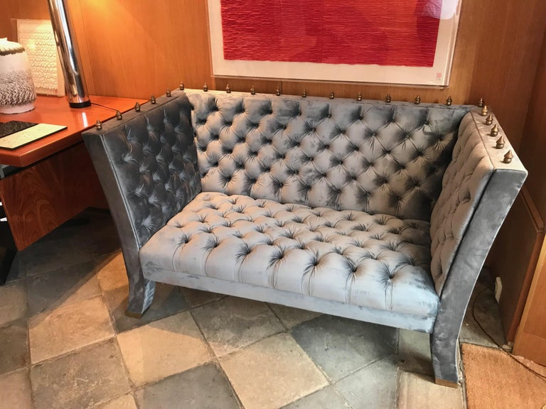 Wide-shape wood sofa upholstered with a grey blue velvet. Quilted fittings. Legs terminating with bronze feet tips. Surmounted with gilt bronze Baroque element.
