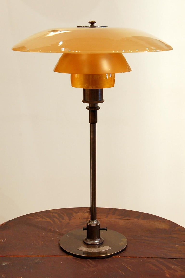 Poul Henningsen (1894 Ordrup, Denmark 1967) Table light, special commission 4/3 amber shades Frame with three cast iron legs marked