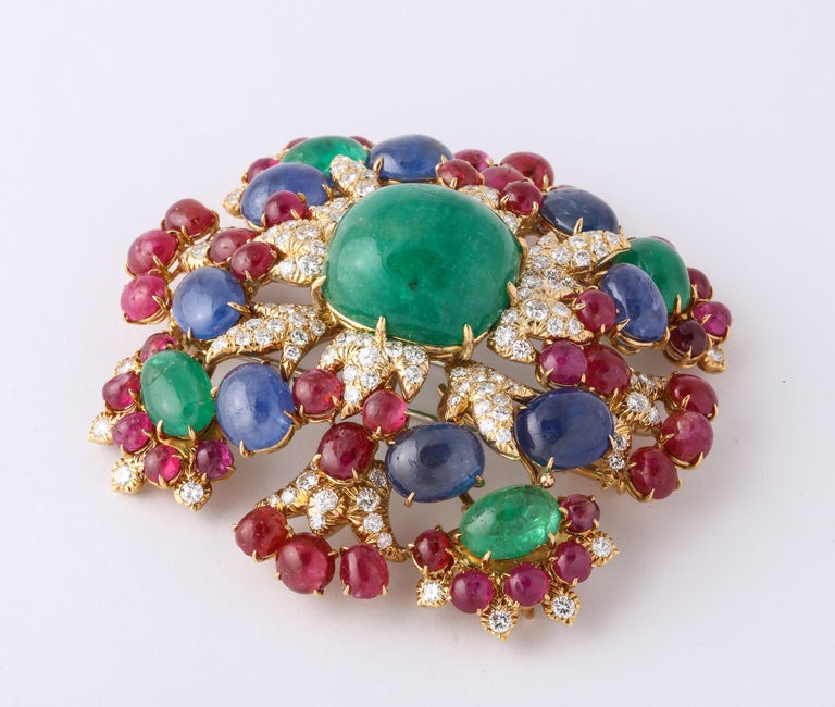 David Webb Brooch  And Pendant in 64 gm of yellow gold, 124 full cut diamonds, 48 natural ruby cabochons,  8 natural sapphire cabochons,  5 natural emerald cabochons. It is marked Webb 18 and can be worn as a pin in a square shape and as a pendant.