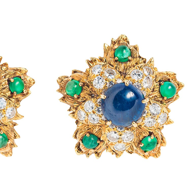 """It's the unique pairing of color and cut that makes these David Webb ear clips stand out. A large central cabochon sapphire is surrounded by faceted diamonds finished off with bright cabochon emeralds.  - 0.81"""" in diameter  - Approximately 9.39"""