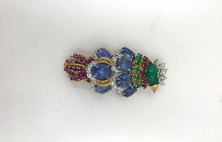 A stylized multi-gem set David Webb brooch, mounted in braided 18k gold with a pointed gold beak, cabochon emerald head & marquise-shaped diamond crest and eye. The plumage predominantly comprises of large seven large cabochon sapphires with diamond