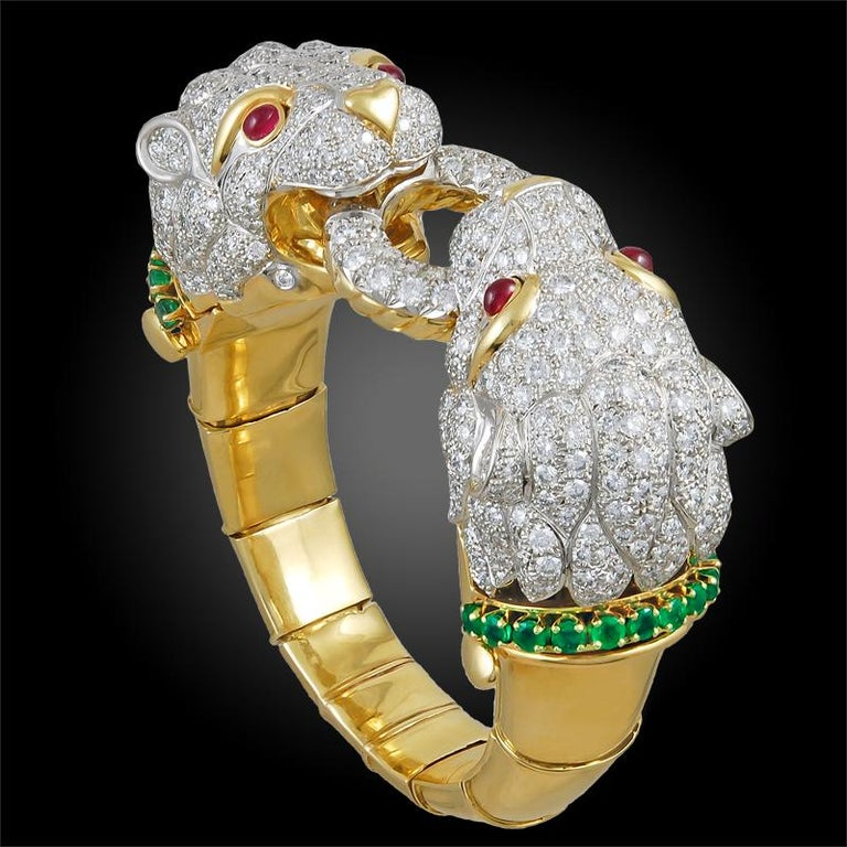 A vintage bangle part of the David Webb 'Kingdom Collection', exquisitely designed as two opposing round brilliant cut diamond filled lion heads on an 18k yellow gold and platinum bangle, each head detailed with round cabochon ruby eyes and an
