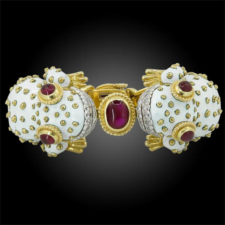 A vintage bangle part of the David Webb 'Kingdom Collection', exquisitely designed as two opposing frog heads, each comprised of white enamel, platinum and 18k yellow gold, featuring cabochon ruby eyes, both grasping a cabochon ruby at the center.