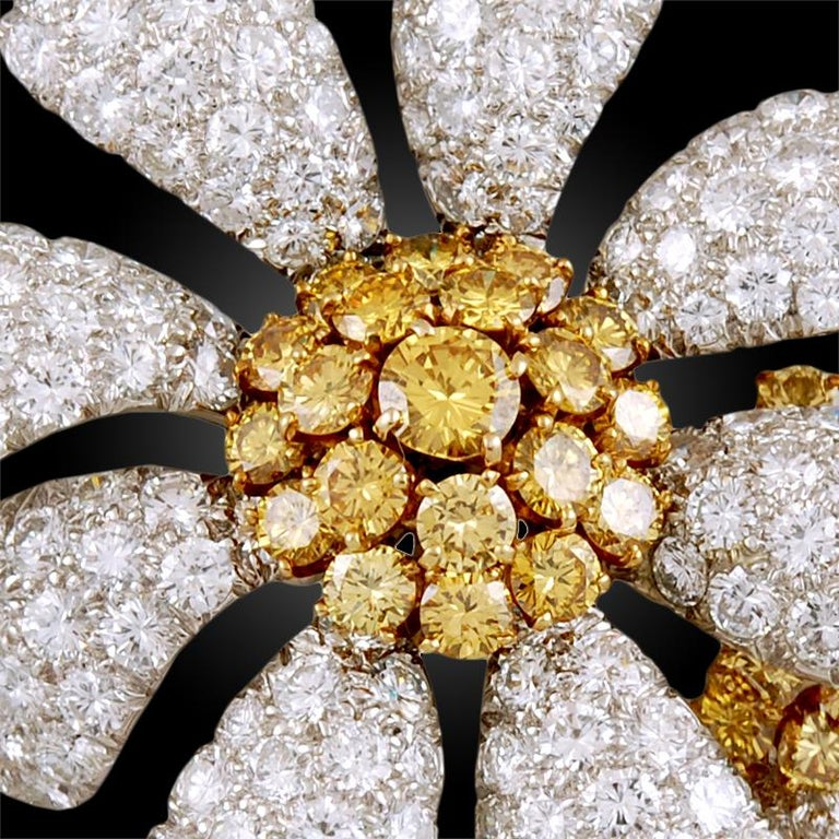 A 1980's David Webb stylized flower brooch in 18k gold and platinum; the entwined daisies set with round diamonds, the flowerheads centered by round diamonds of yellow hue with two marquise-shaped emerald leaves.    Dimensions - approximately 2.5